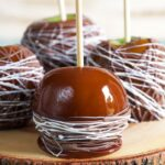 Four caramel apples drizzled with chocolate on a slab of wood.