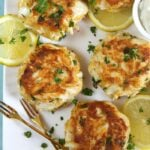 crab cakes on a white platter with gold forks.