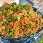 A close up image shows fried rice garnished with freshly chopped green onions.