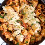 Sliced, cooked chicken breast sits on top of a skillet of spicy rigatoni.