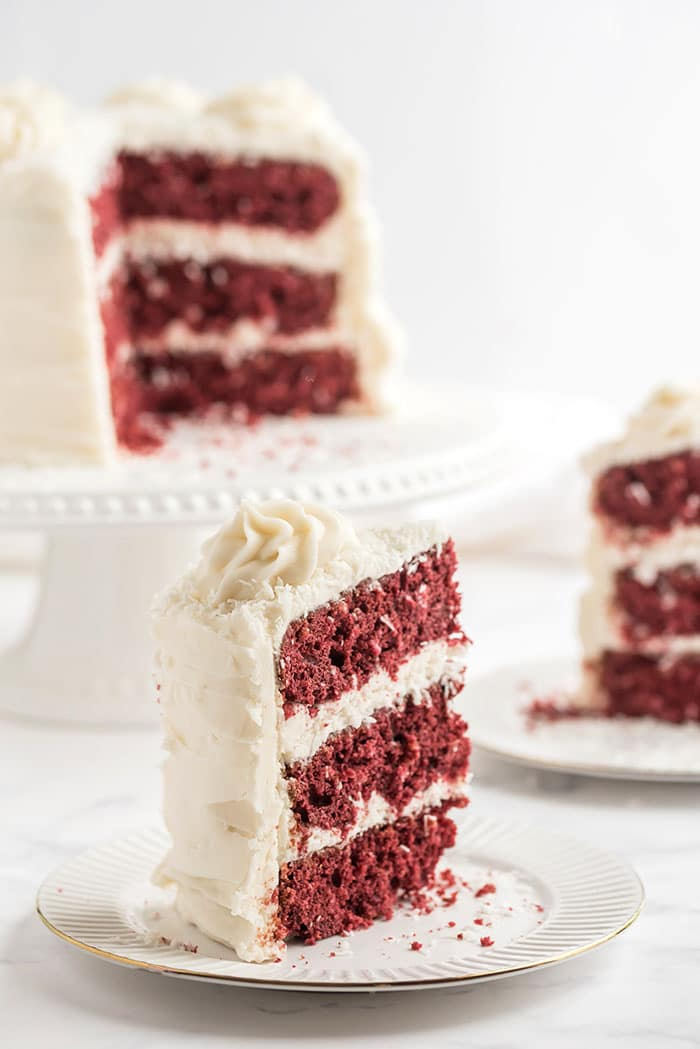 slice of red velvet coconut cake on a white plate with the whole cake in the background.