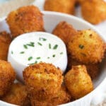 A bowl of potato croquettes is presented with a bowl of sour cream in the middle.