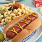 A hot dog is drizzled with ketchup and mustard.