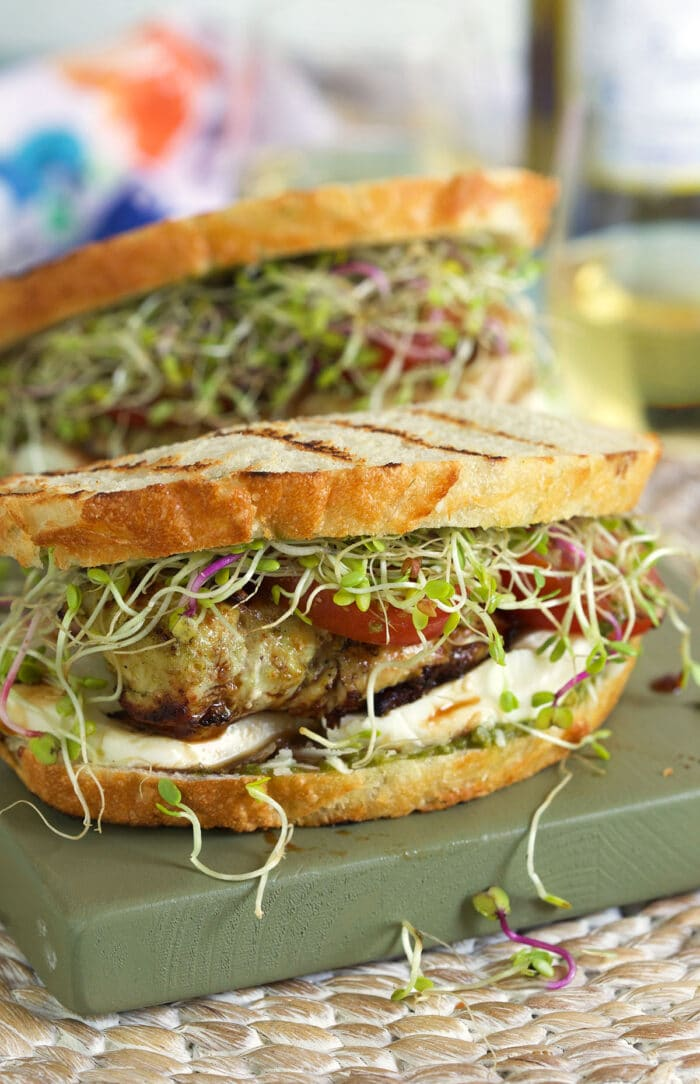 Two chicken sandwiches are assembled on a cutting board.