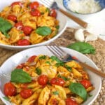 Two white bowls are filled with cheese tortellini and tomatoes.