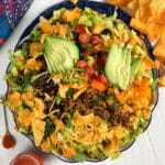 A large bowl is filled to the brim with a Dorito taco salad.