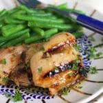 Grilled and glazed chicken thighs are on a plate with green beans.
