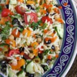 A large ovular bowl is filled with fresh orzo salad.