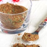 A spoon has a small portion of seasoning on it, next to a glass container of seasoning.