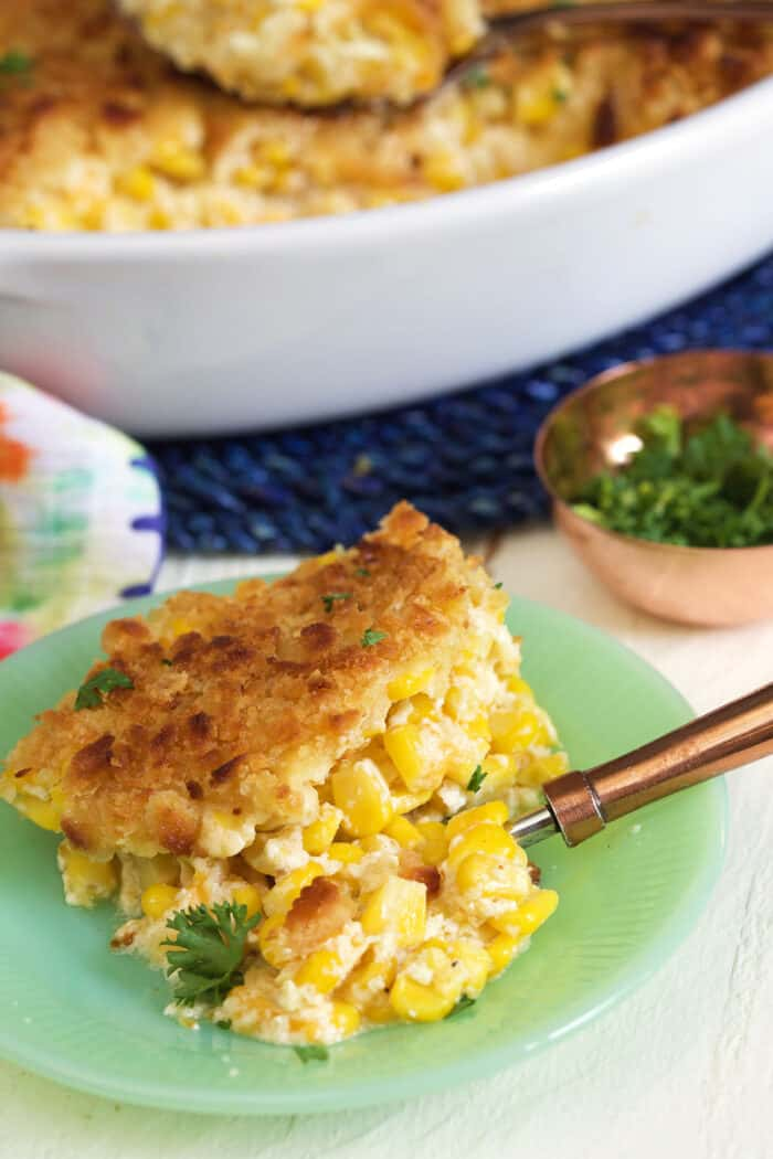 A piece of corn casserole is on a green plate.