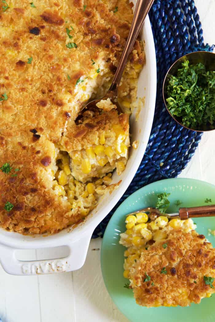 Corn casserole is being scooped from a white dish onto a green plate.