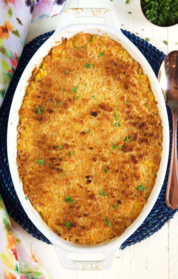 An oval shaped white casserole dish is filled with baked corn casserole.