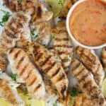 Grilled chicken tenders are placed around a bowl filled with spicy honey mustard.